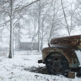 Snowy Arkansas Farm. A fast-moving winter snowstorm covers an old, rusty pickup truck with a barn in the distance.